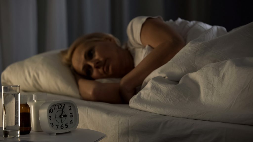 woman lying in bed at night to sleep