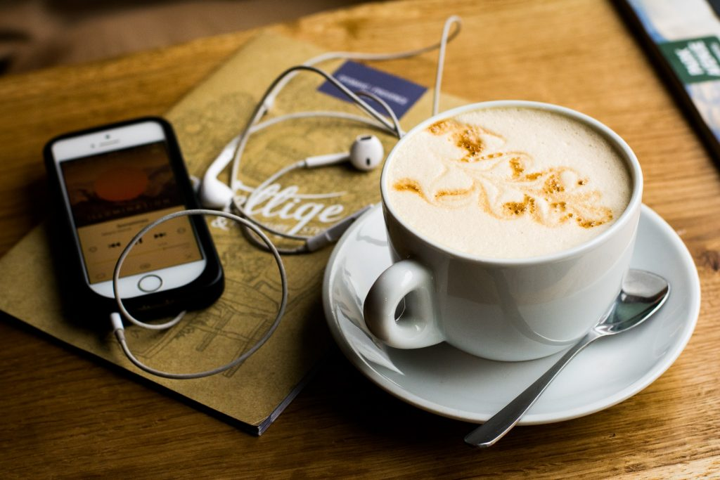A coffee, a notebook, and a phone playing a playlist.