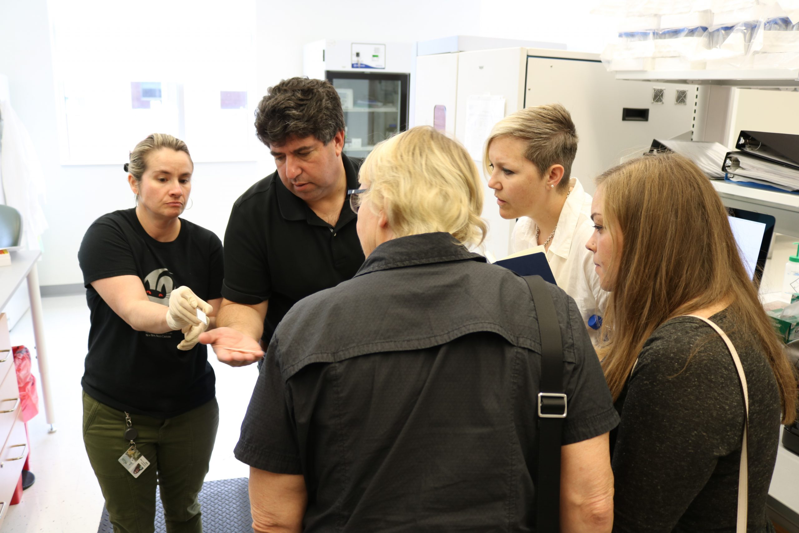 Lyndsay and the Side-Out staff looking at a microscope slide.