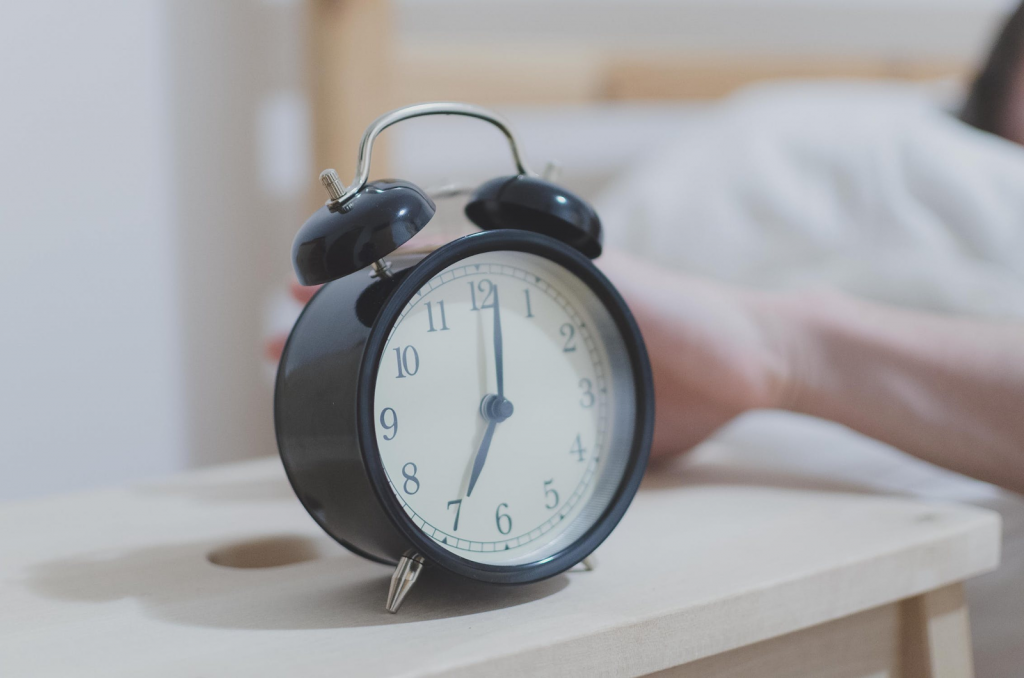 Picture of a hand reaching out to an alarm clock